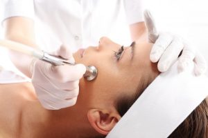 A patient receiving a microdermabrasion treatment. She looks comfortable after her question - does microdermabrasion hurt - is answered by her dermal clinician
